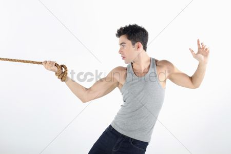 Forbidden : Man with hand tied to a rope  pulling hard