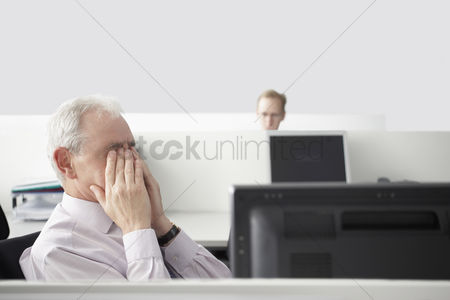 Interior background : Mature businessman sitting rubbing eyes in office cubicle