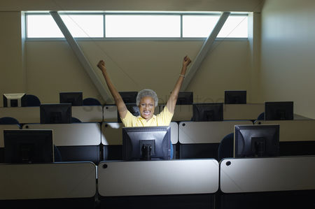 Arm raised : Mature female student celebrating in computer classroom