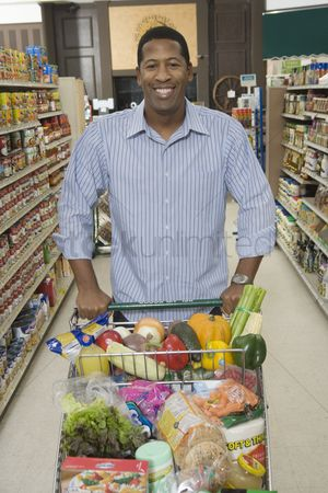 Supermarket : Mature man stands with grocery shopping in supermarket aisle