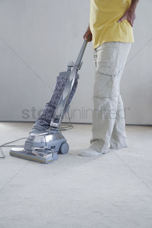Pain : Mature man vacuuming carpet holding lower back in pain low section