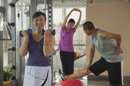Advice : Mature woman lifting weights in the foreground  people exercising in the background