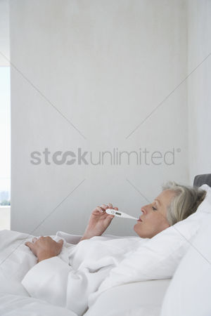 Thermometer : Mature woman lying in bed with thermometer in mouth side view