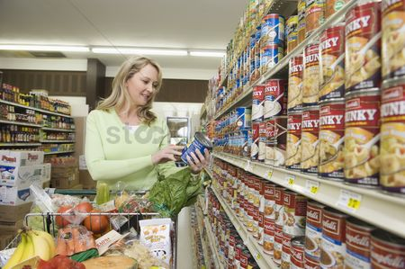 Shopping cart : Mature woman selects tinned goods in supermarket aisle