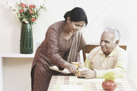 Tea pot : Mature woman serving tea to a mature man