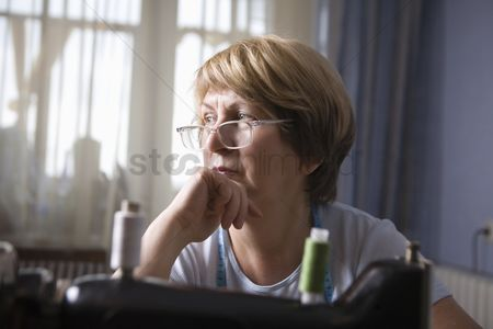 Arts : Mature woman sits leaning on elbow at sewing machine