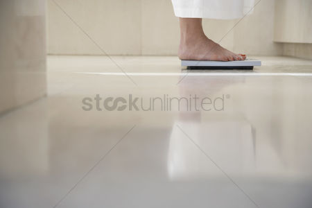 Body : Mature woman standing on scale in bathroom weighing herself low section