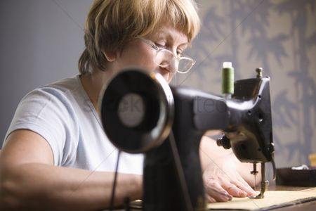 Arts : Mature woman works at sewing machine