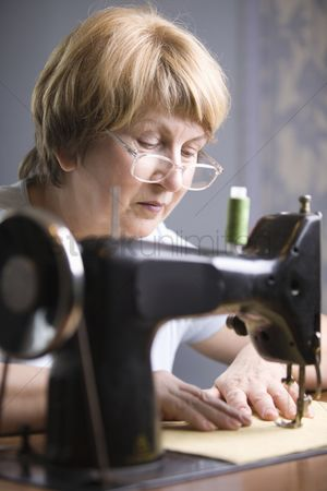 Fixing : Mature woman works at sewing machine