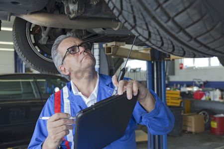 Land : Mechanic analyzing car engine at auto repair shop