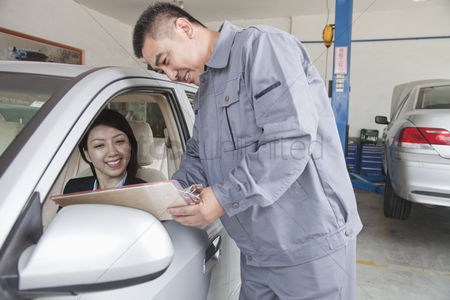 Fixing : Mechanic explaining to businesswoman