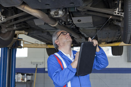 Land : Mechanic scrutinizing the car and writing down something on clipboard