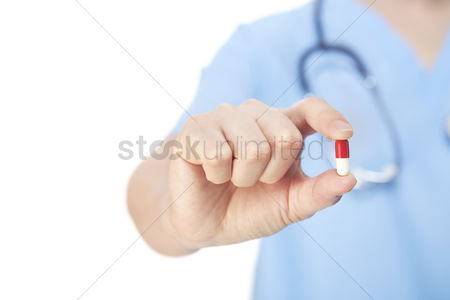 Medication : Medical personnel holding a pill