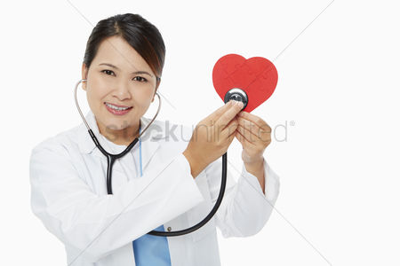 Medical personnel : Medical personnel placing a stethoscope against a red heart