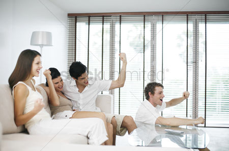 Celebrating : Men and women cheering while watching television at home