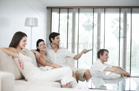 Friends : Men and women watching television at home