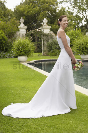 Elegance : Mid adult bride at poolside holding bouquet side view
