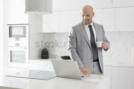 Bald : Mid adult businessman having coffee while using laptop in kitchen