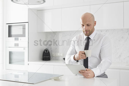Bald : Mid adult businessman having coffee while using tablet pc at kitchen counter