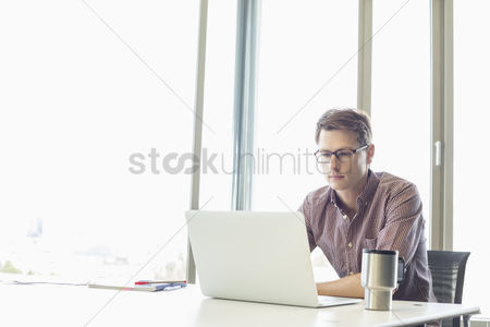Internet : Mid-adult businessman using laptop at desk in creative office