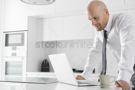 Bald : Mid adult businessman using laptop at kitchen counter