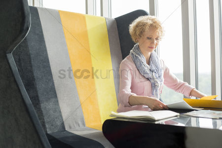 Notepad : Mid adult businesswoman reading documents at desk in office
