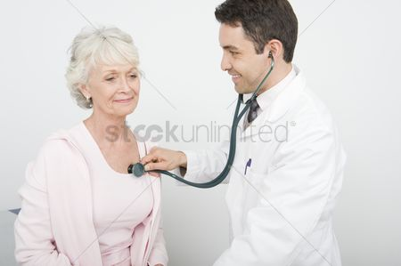 Pink : Mid adult doctor checks breathing of senior patient