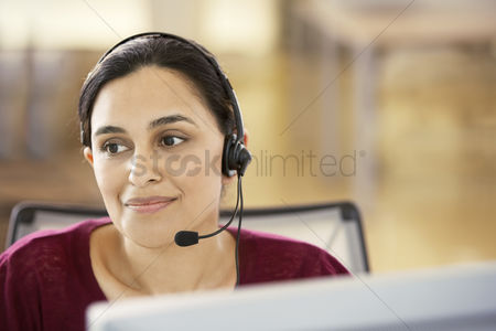 Asian : Mid-adult female office worker sitting in cubicle wearing headset portrait