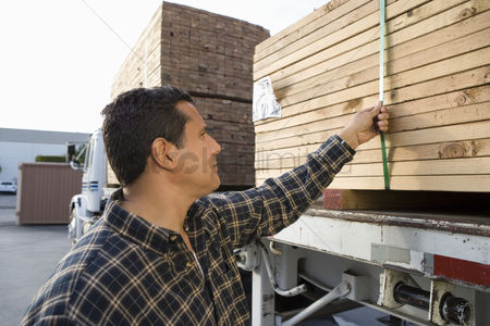 Truck : Mid-adult man checking truck loaded with wood