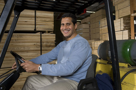 Forklift : Mid-adult man driving forklift at warehouse