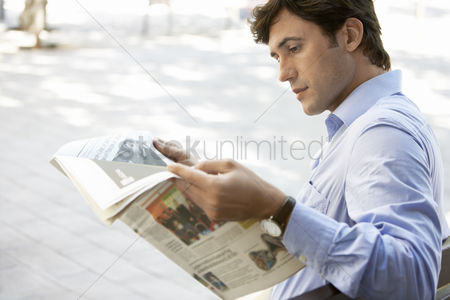Media : Mid-adult man reading newspaper on street