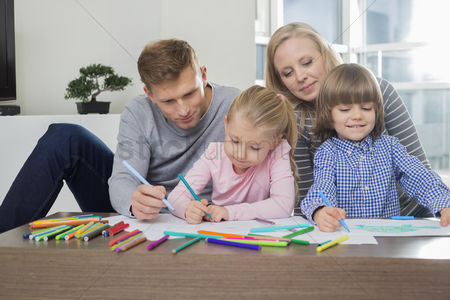 Women : Mid adult parents with children drawing together at home
