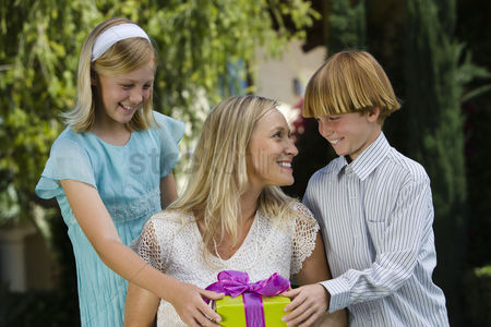 Birthday present : Mid-adult woman receiving birthday present from her son and daughter