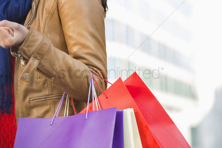 Jacket : Mid section of woman carrying shopping bags