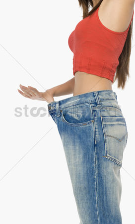 Loss : Mid section view of a woman pulling her jeans