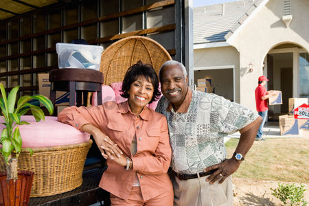 Transportation : Middle-aged couple standing at back of removal van in front of house portrait