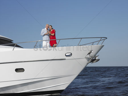 Relationships : Middle-aged couple standing in bow of yacht