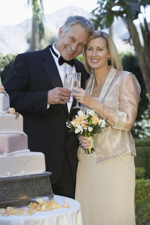 Toasting : Middle-aged couple toasting near wedding cake portrait
