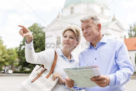 Relationships : Middle-aged woman showing something to man holding map outdoors