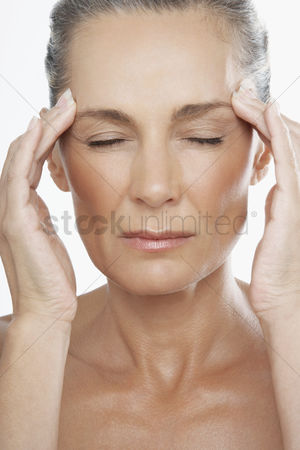 Head shot : Middle-aged woman with fingers on forehead