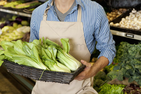Apron : Midsection of man holding basket of bok choy in supermarket