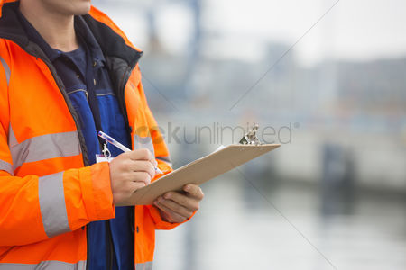Leadership : Midsection of mid adult man writing on clipboard in shipping yard