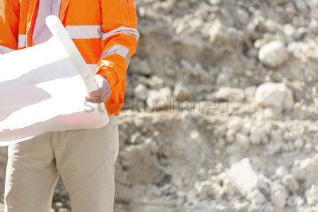 Supervisor : Midsection of supervisor holding blueprint at construction site