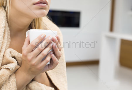 Cold : Midsection of young woman holding coffee mug in house