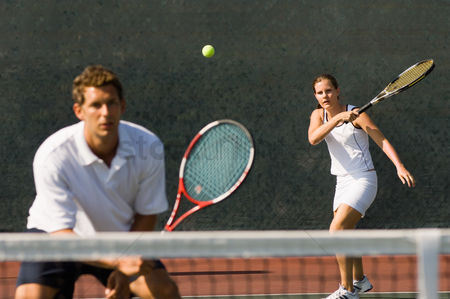 Match : Mixed doubles player hitting tennis ball partner standing near net
