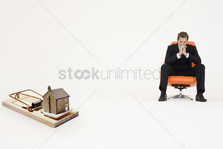 Contemplation : Model home on mouse trap with worried businessman sitting on chair representing increasing real estate rates