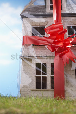 Close : Model house gift-wrapped with red ribbon and bow close-up
