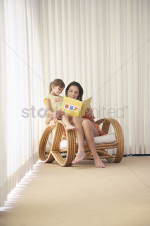 Hispanic : Mother and daughter  5-6  sitting in armchair reading book