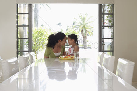 Ponytail : Mother and daughter  5-6 years  sitting at dining table