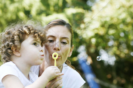 Children playing : Mother and daughter blowing out soap bubbles together